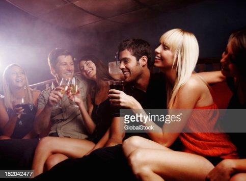 Happy, young amigos mientras disfruta de sus bebidas de cortesía en un club nocturno