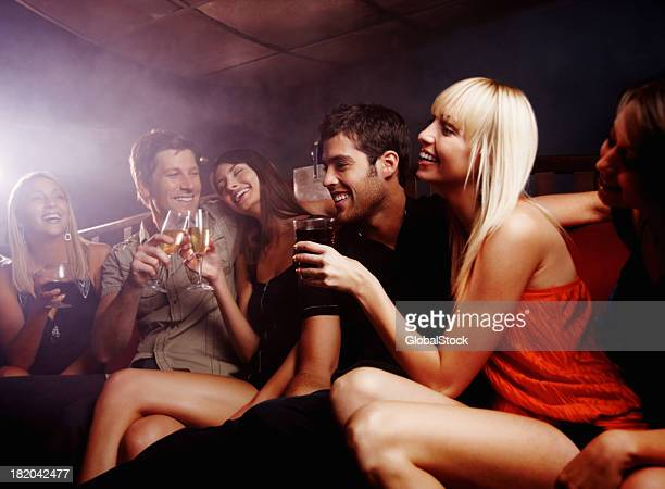 Happy, young friends enjoying their drinks at a night club