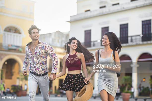 Glückliche junge Freunde laufen gegen Gebäude