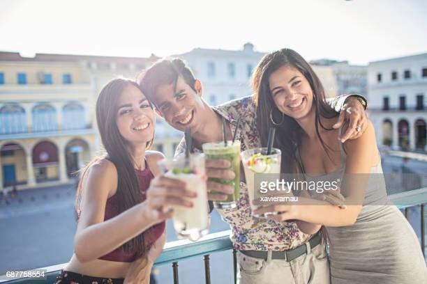 Glückliche junge Freunde, toasten Getränke auf Balkon