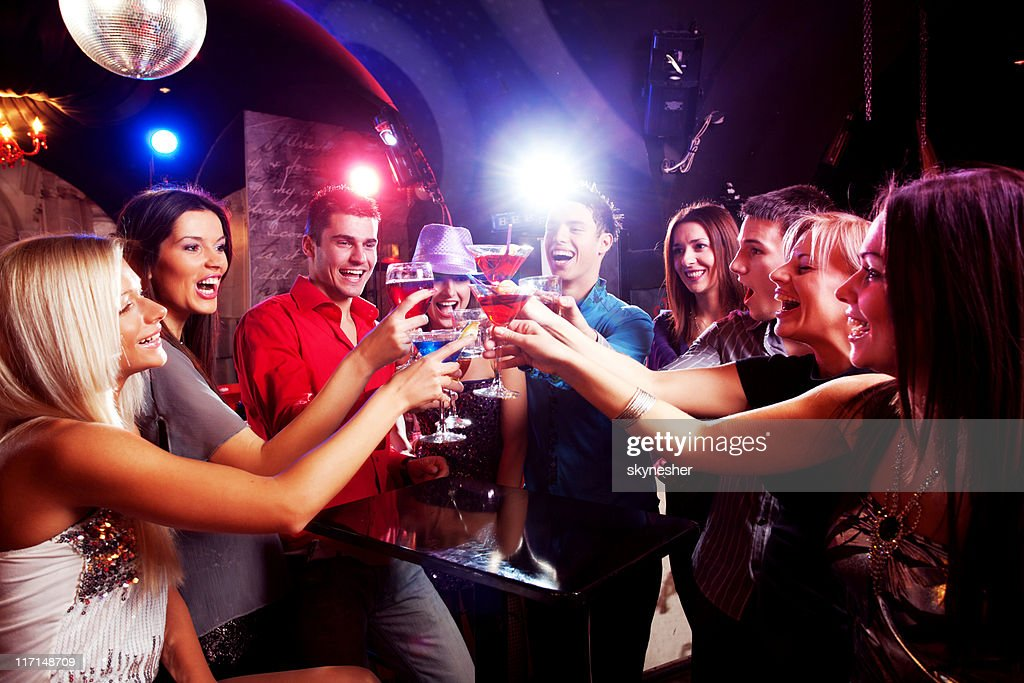 Happy young friends touching the glasses with each other. : Stock Photo