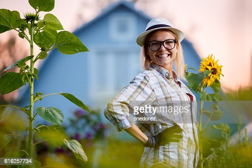 Happy young gardener posing in garden before her cottage : Foto de stock