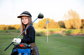 A beautiful young girl playing golf at her local golf course.