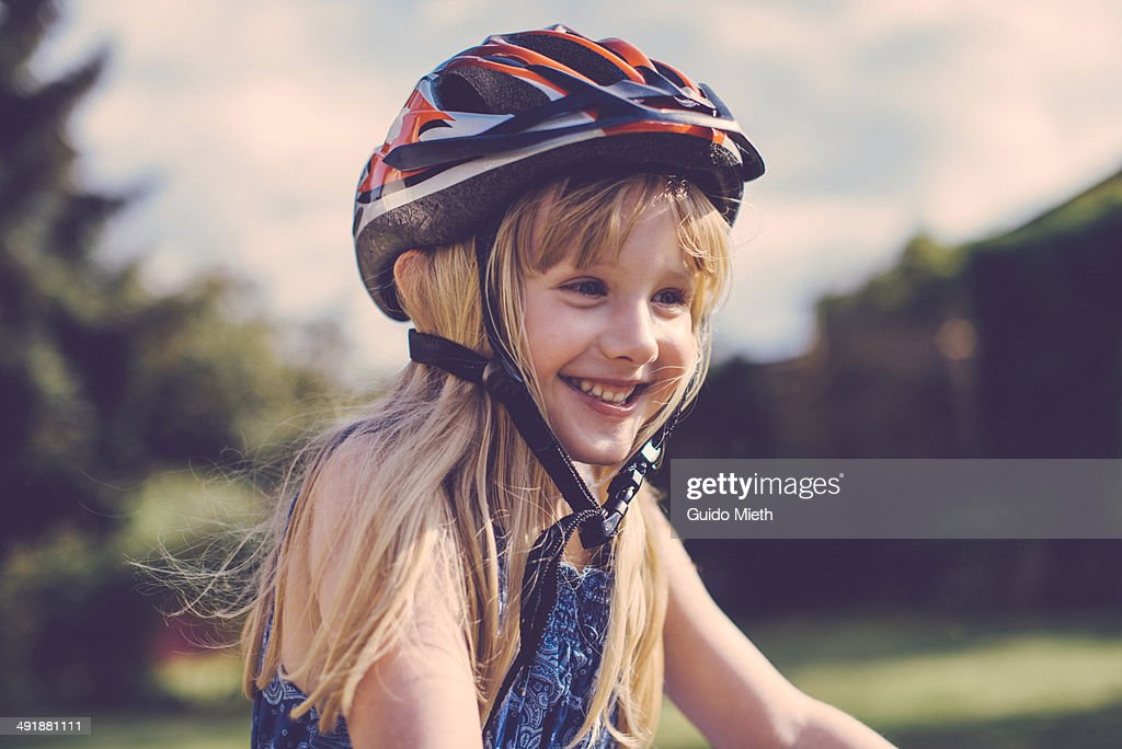 Happy young girl cycling.