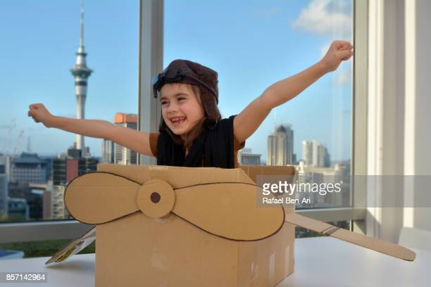 Happy young girl flying a cardboard airplane above city