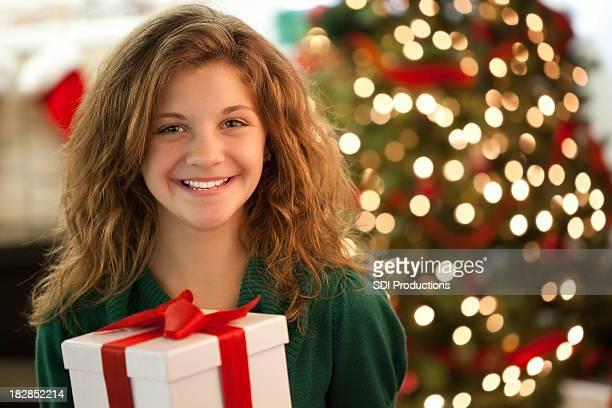 Jeune fille heureuse tenant cadeau enveloppé dans la salle de séjour