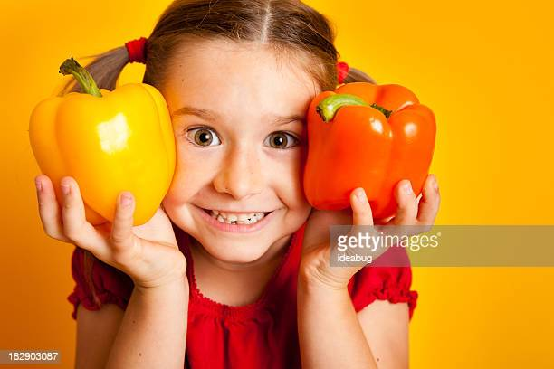 Happy Young Girl Holding Yellow and Orange Bell Peppers