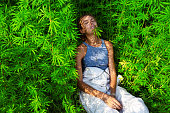 Happy young girl in a bush marijuana