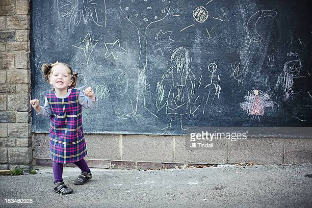 happy young girl in front of blackboard drawings