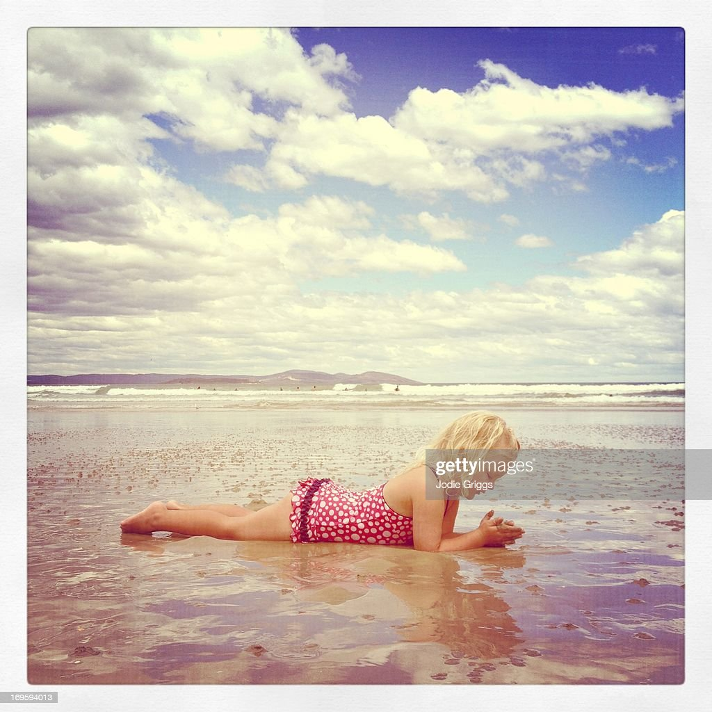 Happy young girl playing in sand at the beach : Stock Photo