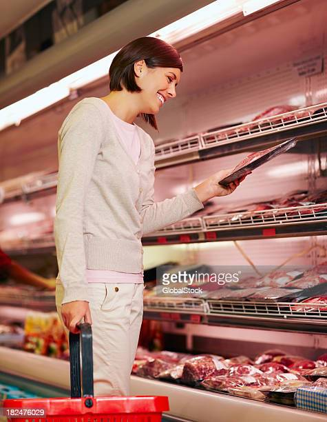 Happy young girl purchasing a packet of meat