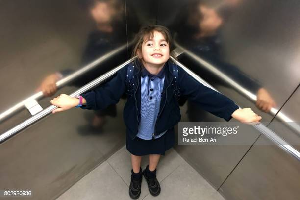 Happy young girl standing in elevator