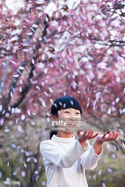 Happy young girl throwing cherry blossom petals in the air outside in a park in springtime