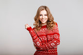 Happy young girl with a smile in a winter red vintage sweater on a gray background
