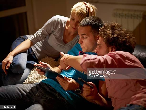 Glückliche junge Gruppe von Menschen, die Spaß mit digitalen tablet