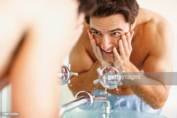 幸せな若い男彼の顔を洗うの洗面台