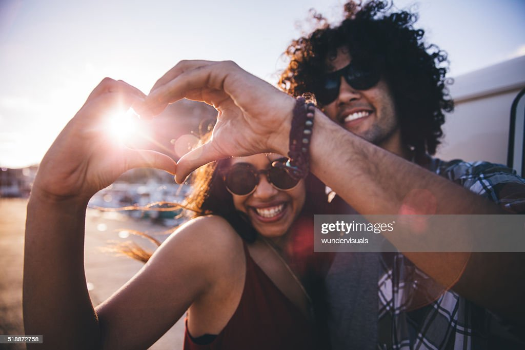 Happy young hipster couple making heart shape with hands : Stock Photo