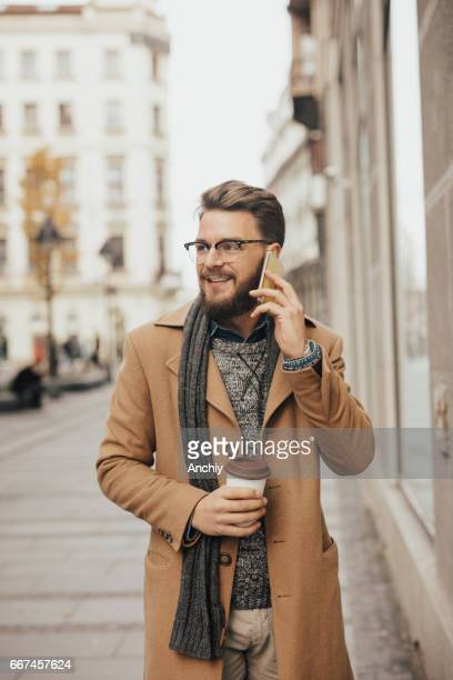 Happy young hipster walking in town and talking on mobile phone