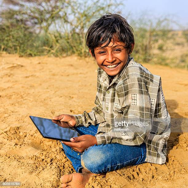 Happy young Indian boy using digital tablet, desert village, India