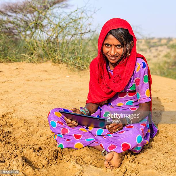 Happy young Indian girl using digital tablet, desert village, India