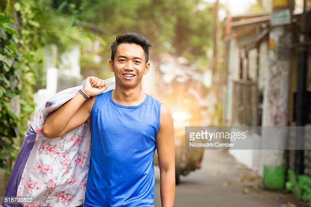 Happy young Indonesian man carrying dry cleaning