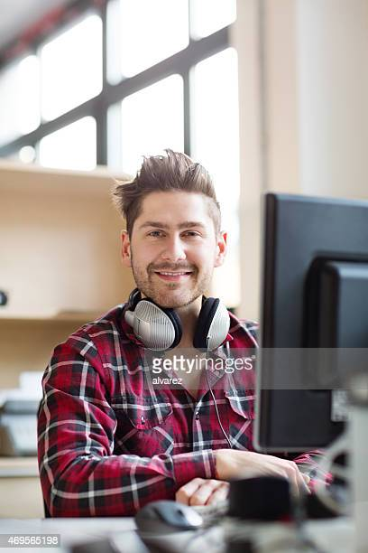 Happy young IT professional at his desk