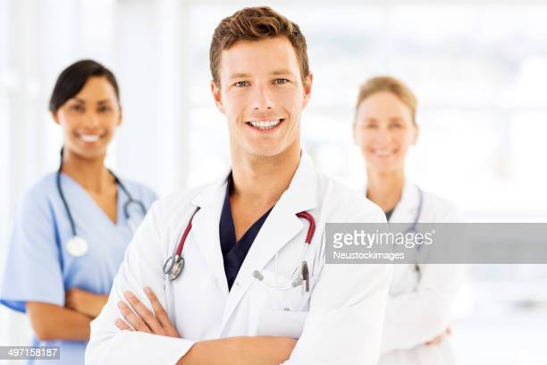 Happy Young Male Doctor With Medical Team
