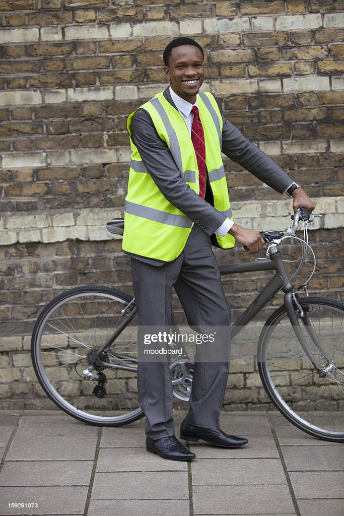Happy young male engineer with bicycle against brick wall : Stock Photo