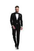 happy young male fashion model in tuxedo is walking on white background