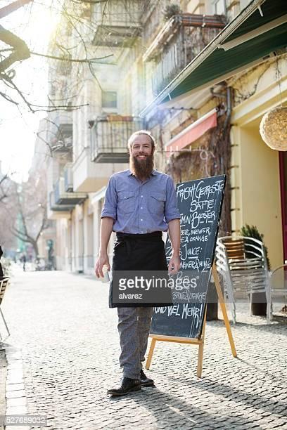 Feliz jovem empregado de mesa masculino em pé fora do café
