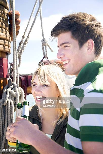 Happy young man and woman clinking beer bottles on a sailing ship