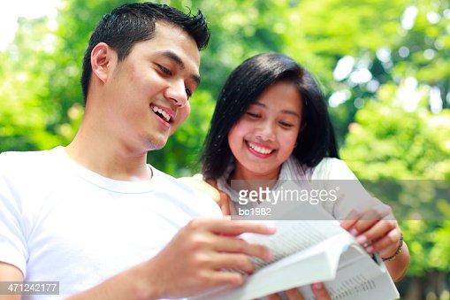 Glücklicher junger Mann und Frau liest Buch