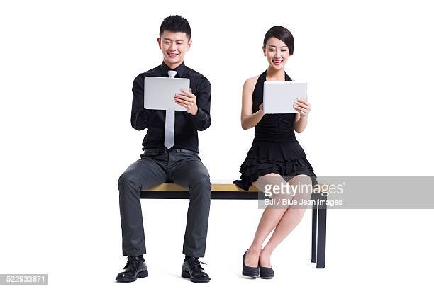 Happy young man and woman with digital tablets