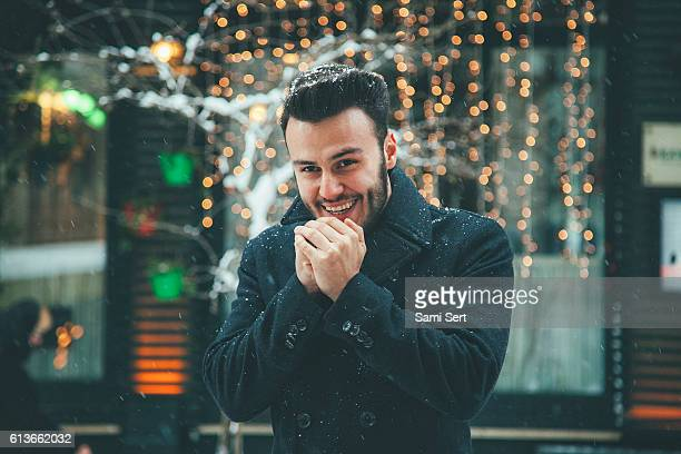 Happy Young man blowing on hands in winter
