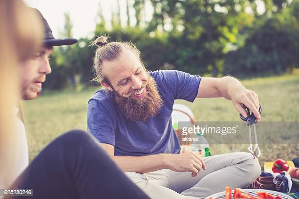 Happy young man cooking on barbecue at park
