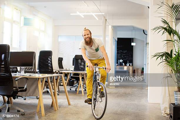 Happy young man cycling in a startup