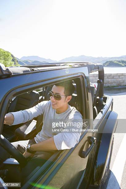 Happy young man driving a jeep