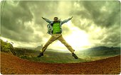 Happy Young Man Jumping Against Overcast Sky In Excitement