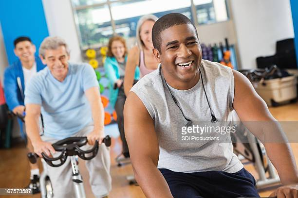 Happy young man leading his fitness club's cycling class