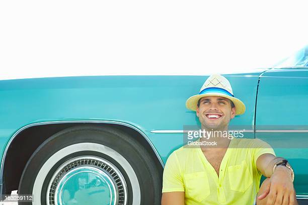 Happy young man leaning on his car against sky