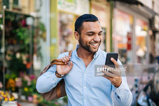 Happy young man looking at his phone