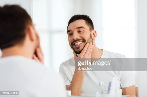 happy young man looking to mirror at home bathroom : Stock Photo