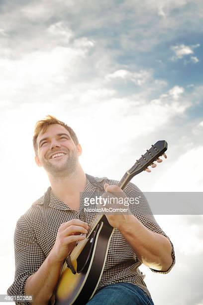 Happy young man playing the mandoline outdoors