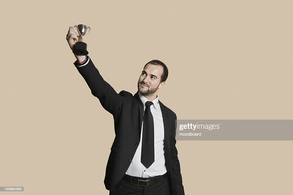 Happy young man raising winning trophy over colored background