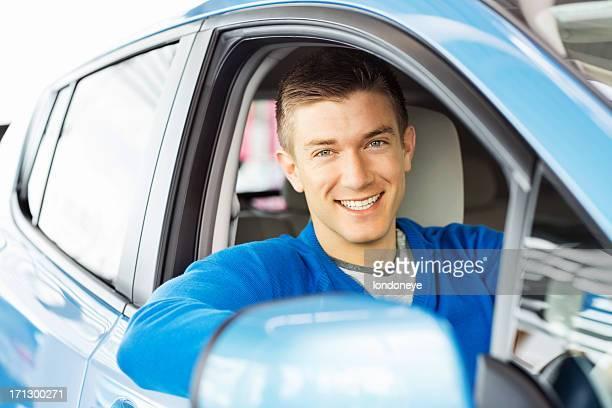Felice giovane uomo seduto In auto nuova