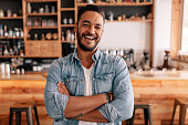 Portrait of happy young man standing with his arms crossed in a cafe. Smiling handsome guy standing in a coffee shop.