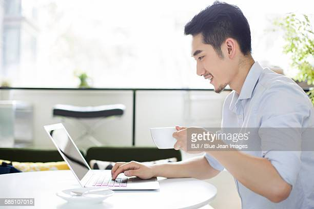 Happy young man using laptop in coffee shop
