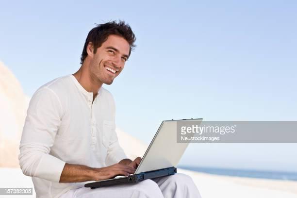 Heureux jeune homme à l'aide de portable sur la plage