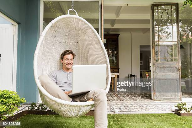 Happy young man using laptop on swing chair