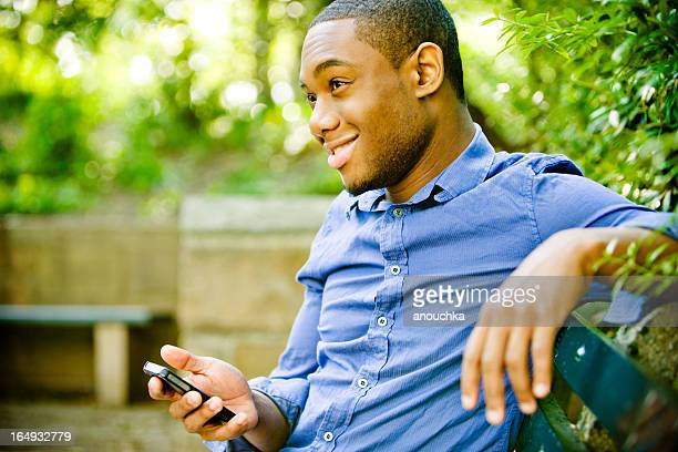 Happy Young Man Using Mobile phone outdoors